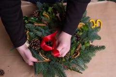 Kerstmis natuurlijke kroon De bloemists handen die natuurlijke Kerstmiskroon, Kerstmisdecoratie met natuurlijke spar maken vertak royalty-vrije stock foto