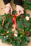 Kerstmis natuurlijke kroon De bloemists handen die natuurlijke Kerstmiskroon, Kerstmisdecoratie met natuurlijke spar maken vertak royalty-vrije stock afbeeldingen