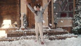 Kerstmis of nieuw jaar portret van een kind in Kerstmisdecoratie het meisje in een bonthoofdtelefoons werpt op de sneeuw stock footage