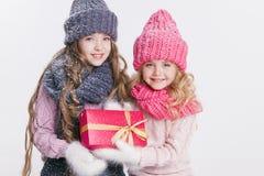 Kerstmis Nieuw jaar Twee kleine zusters die in de winterkleren huidig houden Roze en grijze hoeden en sjaals Familie De winter Royalty-vrije Stock Afbeeldingen