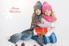 Kerstmis Nieuw jaar Twee kleine zusters die en in de winterkleren huidig koesteren houden Roze en grijze hoeden en sjaals Stock Fotografie