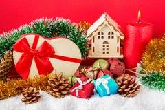 Kerstmis of nieuwe jaarkaart Brandende rode kaars, kegels, giftboxes, decoratief huis, speelgoed en lovertje tegen rode achtergro Royalty-vrije Stock Foto's