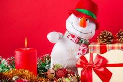 Kerstmis of nieuwe jaarkaart Grappige sneeuwman met het branden van kaars, kegels, giftbox anf lovertje tegen rode achtergrond Stock Foto's