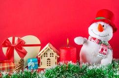 Kerstmis of nieuwe jaarkaart Grappige sneeuwman met het branden van kaars, kegels, giftbox op groen klatergoud tegen rode achterg Stock Fotografie