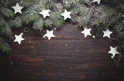 Kerstmis of Nieuwjaarachtergrond: bont-boom takken, decoratie en schitterende sterren op houten, hoogste mening, exemplaarruimte Stock Foto's