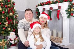 Kerstmis of Nieuwjaarviering Gelukkige jonge familiezitting dichtbij Kerstboom met Kerstmisgiften Een open haard met Kerstmis sto Royalty-vrije Stock Afbeelding