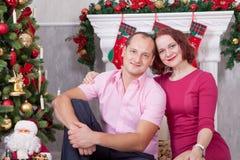 Kerstmis of Nieuwjaarviering Het jonge paar zit en omhelst in Kerstmisbinnenland, dichtbij de open haard, Kerstboom Gelukkig H Stock Afbeeldingen