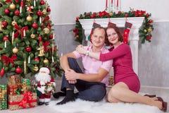 Kerstmis of Nieuwjaarviering Het jonge paar zit en omhelst in Kerstmisbinnenland, dichtbij de open haard, Kerstboom Gelukkig H Royalty-vrije Stock Afbeeldingen