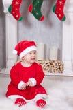 Kerstmis of Nieuwjaarviering Het meisje gekleed in een rood feestelijk kostuum van gnoom en santahoed, zit op de vloer dichtbij C Stock Fotografie
