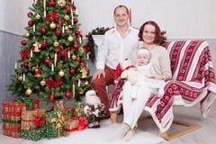 Kerstmis of Nieuwjaarviering Portret van vrolijke jonge familie van drie mensen dichtbij de Kerstboom met Kerstmisgiften FI Stock Foto's