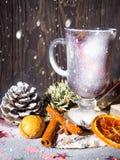 Kerstmis overwoog wijn met kruiden in glasswithplaid en sneeuw op een Kerstmisboom op donkere achtergrond, de glaskop van royalty-vrije stock afbeeldingen