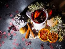 Kerstmis overwoog wijn met kruiden in glasswithplaid en sneeuw op een Kerstmisboom op donkere achtergrond, de glaskop van stock foto