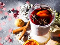 Kerstmis overwoog wijn met kruiden in glasswithplaid en sneeuw op een Kerstmisboom op donkere achtergrond, de glaskop van royalty-vrije stock foto