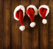 Kerstmis Santa Claus Hats Hanging op Hout, Kerstmisfamilie stock foto's