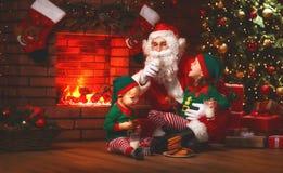 Kerstmis Santa Claus met Elf drinkt Melk en eet Koekjes Stock Fotografie