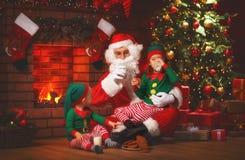 Kerstmis Santa Claus met Elf drinkt Melk en eet Koekjes Stock Afbeelding