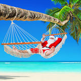 Kerstmis Santa Claus ontspant in hangmat in tropisch Palm Beach Royalty-vrije Stock Foto's