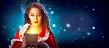 Kerstmis Schoonheids donkerbruine jonge vrouw in partijkostuum het openen giftdoos over de achtergrond van de vakantienacht stock foto's