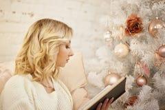 Kerstmis, vakantie en mensenconcept - het gelukkige jonge boek van de vrouwenlezing thuis Stock Afbeelding