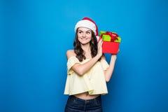 Kerstmis, vakantie, viering en mensenconcept - glimlachende vrouw in rode kleding met giftdozen over blauwe achtergrond stock foto