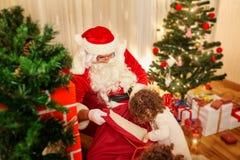 In Kerstmis verdeelt Santa Claus giften aan kinderen uit Th royalty-vrije stock afbeelding