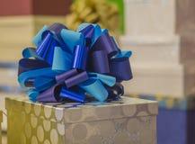 Kerstmis of verjaardagsgift gouden doos met blauwe lint dichte omhooggaand Royalty-vrije Stock Afbeeldingen