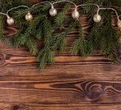 Kerstmis vierkante samenstelling met uitstekende slinger en spartakken op houten achtergrond koordlichten Stock Fotografie