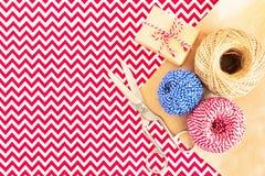 Kerstmis vlak-legt van giftvakje, broodjes van koorden, het verpakkende document van kraftpapier en schaar op rood met wit stoffe stock fotografie