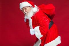 Kerstmis Vriendelijke en vermoeide Santa Claus in witte handschoenen draagt een rode zak met giften over zijn schouder Op rood royalty-vrije stock fotografie
