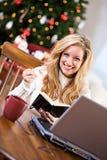 Kerstmis: Vrouw die in Notitieboekje schrijven terwijl online Stock Afbeeldingen