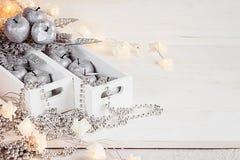 Kerstmis zachte zilveren appelen en lichten die in dozen op een houten witte achtergrond branden Royalty-vrije Stock Foto