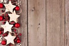 Kerstmis zijgrens met rustieke houten sterornamenten en snuisterijen op oud hout Stock Foto