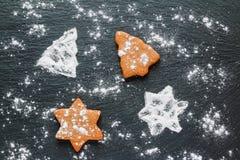 Kerstmis zwarte achtergrond met suikerglazuursuiker en bruine chocolade en gemberkoekjes in vorm van spar en ster, hoogste mening Stock Foto