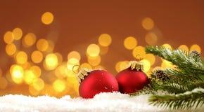 Kerstmisachtergrond - de de Kerstmisballen en pijnboom vertakken zich in de sneeuw met vage lichten royalty-vrije stock fotografie