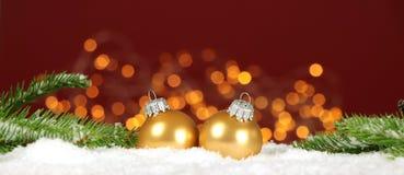 Kerstmisachtergrond - de de Kerstmisballen en pijnboom vertakken zich in de sneeuw met vage lichten stock afbeeldingen