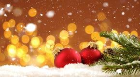 Kerstmisachtergrond - de de Kerstmisballen en pijnboom vertakken zich in de sneeuw met vage lichten stock foto