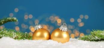 Kerstmisachtergrond - de de Kerstmisballen en pijnboom vertakken zich in de sneeuw met vage lichten stock afbeelding