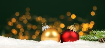 Kerstmisachtergrond - de de Kerstmisballen en pijnboom vertakken zich in de sneeuw met vage lichten stock foto's