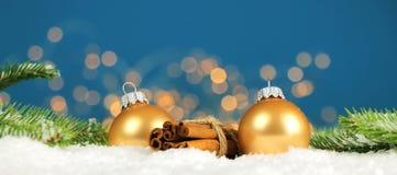 Kerstmisachtergrond - de Kerstmisballen en de pijpjes kaneel met pijnboom vertakken zich in de sneeuw met vaag licht royalty-vrije stock afbeeldingen