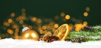 Kerstmisachtergrond - de Kerstmisballen en de pijpjes kaneel met pijnboom vertakken zich in de sneeuw met vaag licht stock foto's