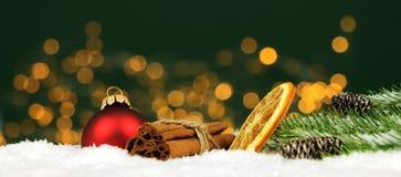 Kerstmisachtergrond - de Kerstmisballen en de pijpjes kaneel met pijnboom vertakken zich in de sneeuw met vaag licht stock afbeeldingen