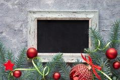 Kerstmisachtergrond met bord, de takjes van de Kerstmisboom en snuisterijen op grijs stock fotografie