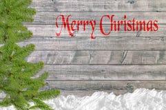 Kerstmisachtergrond met de boom van de sneeuwpijnboom en Vrolijke Kerstmis Royalty-vrije Stock Afbeelding