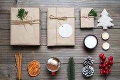 Kerstmisachtergrond met met de hand gemaakte huidige giftdozen en rustieke decoratie op uitstekende houten raad Royalty-vrije Stock Foto's