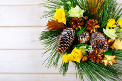 Kerstmisachtergrond met gele zijderozen en gouden denneappel stock fotografie