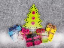 Kerstmisachtergrond met gevoelde decoratie: Kerstboom en kleurrijke giften Stock Afbeeldingen