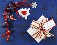 Kerstmisachtergrond met gevoelde decoratie op donkerblauw uitstekend hout met witte gift Royalty-vrije Stock Foto