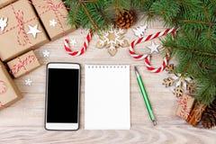 Kerstmisachtergrond met giftvakjes, mobiele telefoon met het achterscherm en leeg notitieboekje, exemplaarruimte Malplaatje voor  stock foto