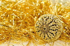 Kerstmisachtergrond met goud gesneden bal en gouden klatergoud. Stock Foto