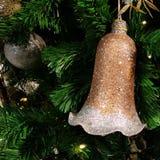 Kerstmisachtergrond met gouden klokken op de Kerstboom Royalty-vrije Stock Afbeeldingen